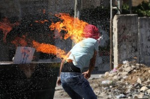 Palestinian protesters put out a fire burning on a compatriot, caused by a molotov cocktail which he was trying to hurl at Israeli troops during clashes in the West Bank city of Hebron, October 13, 2015.